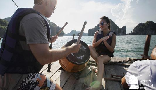 Un couple profite de leur croisière sur la jonque Secret d'Halong pour faire des activités, comme ici la pêche.